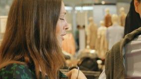 A menina de sorriso tenta sobre vestidos da forma no espelho com noivo video estoque