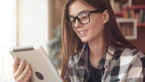 A menina de sorriso usa a tabuleta vídeos de arquivo