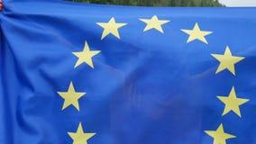 Menina de surpresa com a bandeira da União Europeia que está indo estudar na UE que sorri e que olha a câmera sobre filme