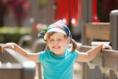 Menina de três anos de riso na área do campo de jogos Fotografia de Stock Royalty Free