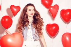 Menina de Valentine Beauty com os balões de ar vermelhos que ri, no fundo branco Mulher nova feliz bonita O dia da mulher Festa n foto de stock