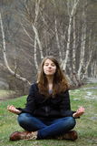 A menina de Youngl que senta-se na grama e medita Imagem de Stock