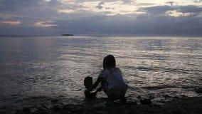 Menina de Yuong que joga com o navio do brinquedo na praia filme