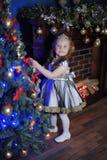 A menina decora a árvorede Natal de Foto de Stock Royalty Free