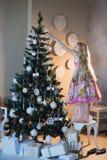 A menina decora os brinquedos da árvore de Natal, a alegria, a preparação para o feriado, empacotando, caixas, Natal, ano novo, l Imagens de Stock