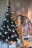 A menina decora os brinquedos da árvore de Natal, a alegria, a preparação para o feriado, empacotando, caixas, Natal, ano novo, l Foto de Stock