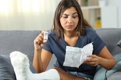 Menina deficiente confusa que lê um folheto de comprimidos do analgésico imagens de stock royalty free