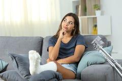 Menina deficiente que pensa olhando o lado em casa foto de stock