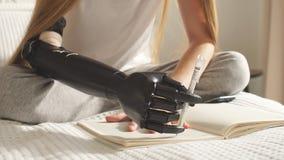 A menina deficiente tenta guardar uma pena com um braço artificial vídeos de arquivo