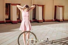 A menina deixou cair e quebrou a bicicleta a emoção foi amedrontada e não conhece o que fazer foto de stock