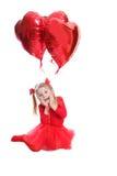 Menina deleitada no vermelho com balões coração-dados forma imagem de stock