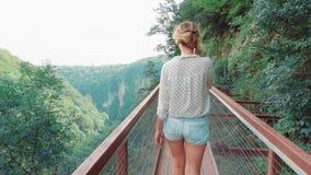 Menina delgada alta com caminhadas do cabelo louro sobre a ponte sobre a floresta verde-clara na roupa ocasional, senhora em curt filme