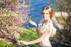 Menina delgada bonita com cabelo louro em um vestido leve longo contra o contexto da natureza, árvores de florescência, mar azul, Imagem de Stock