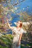 Menina delgada bonita com cabelo louro em um vestido leve longo contra o contexto da natureza, árvores de florescência, mar azul, Foto de Stock