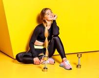 A menina delgada bonita com o cabelo louro longo vestido em um sportswear à moda está sentando-se no assoalho amarelo ao lado do imagens de stock