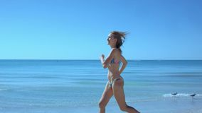 Menina delgada bonita no biquini que corre ao longo da praia ao longo da costa do oceano, cabelo que acena pelo vento, corredor ' vídeos de arquivo