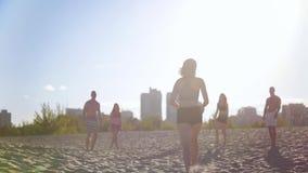 A menina delgada bonita nova corre com uma bola do voleibol a seus amigos, há um jogo do voleibol de praia vídeos de arquivo
