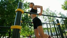 A menina delgada em um terno preto dos esportes executa exercícios da força no simulador no parque video estoque