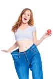 A menina delgada feliz mostra o resultado de uma dieta da maçã Fotografia de Stock