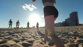 A menina delgada nova corre e faz a bola passar a seus amigos ao jogar o voleibol de praia vídeos de arquivo