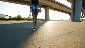Menina delgada nova que monta um skate sob a ponte e as quedas vídeos de arquivo