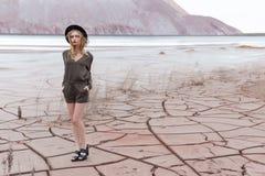Menina delgada 'sexy' bonita em um chapéu negro nas montanhas com um forte vento Imagens de Stock Royalty Free