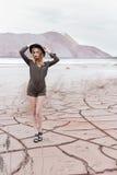 Menina delgada 'sexy' bonita em um chapéu negro nas montanhas com um forte vento Fotografia de Stock Royalty Free