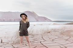 Menina delgada 'sexy' bonita em um chapéu negro nas montanhas com um forte vento Imagens de Stock