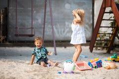 A menina derrama a água de uma menina do potLittle da mangueira que joga na jarda com seu irmão fotografia de stock