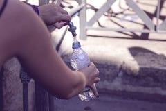 A menina derrama a água em uma garrafa da fonte da rua fotos de stock