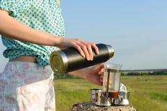A menina derrama a água a ferver da garrafa térmica na imprensa do francês com café no fundo da paisagem do campo do verão imagens de stock