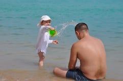 A menina derrama a ?gua em seu pai Espirra da ?gua no mar Crian?a e pai em f?rias imagens de stock royalty free