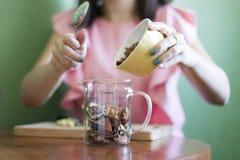 A menina derrama maçãs secadas em um copo de medição na cozinha na tabela fotos de stock