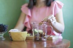 A menina derrama maçãs secadas em um copo de medição na cozinha na tabela foto de stock
