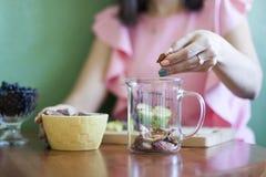 A menina derrama maçãs secadas em um copo de medição na cozinha na tabela fotografia de stock