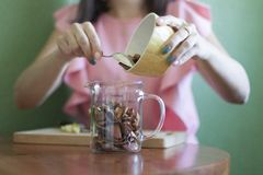 A menina derrama maçãs secadas em um copo de medição na cozinha na tabela imagens de stock