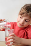 A menina derrama para fora a água de um vidro a outro Fotografia de Stock Royalty Free