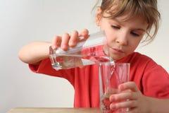 A menina derrama para fora a água de um vidro a outro Fotos de Stock Royalty Free