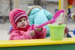 A menina derrama a areia na cubeta na caixa de areia Fotos de Stock Royalty Free