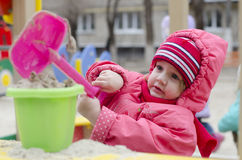 A menina derrama a areia na cubeta na caixa de areia Fotografia de Stock Royalty Free
