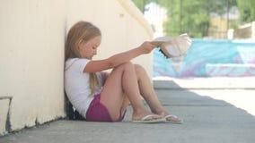 Menina desabrigada que implora a esmola na rua em um close-up do dia de verão filme