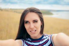 Menina desajeitada que tenta tomar um Selfie na natureza imagem de stock