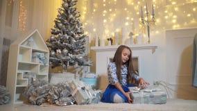 A menina desata uma curva em uma caixa com um presente vídeos de arquivo