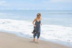 menina descalça bonita no vestido longo que corre na praia fotografia de stock royalty free