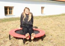 Menina descalça que senta-se no trampolim fotografia de stock royalty free