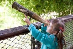 A menina descobre através do telescópio antiquado Imagens de Stock
