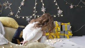 A menina desdobra um presente do Natal na perspectiva de uma festão vídeos de arquivo