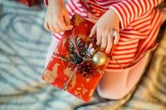 A menina desembala uma caixa de presente decorada do Natal Close-up Th foto de stock