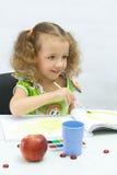 A menina desenha por pinturas fotografia de stock royalty free