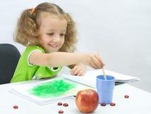 A menina desenha por pinturas fotografia de stock